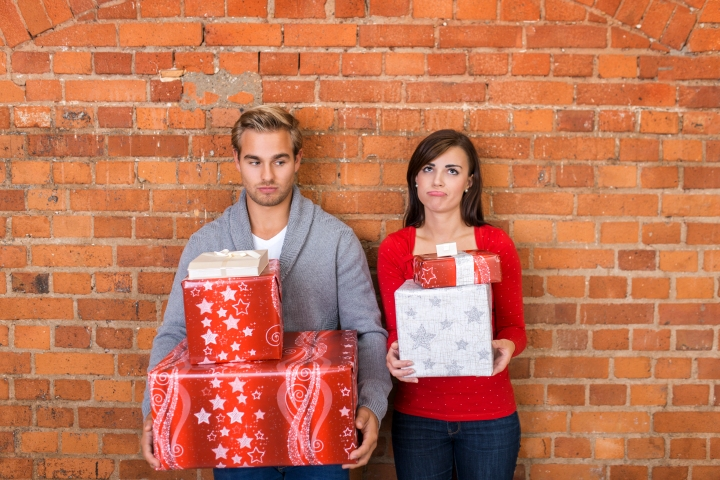 Frowning Lovers Holding Christmas Gifts
